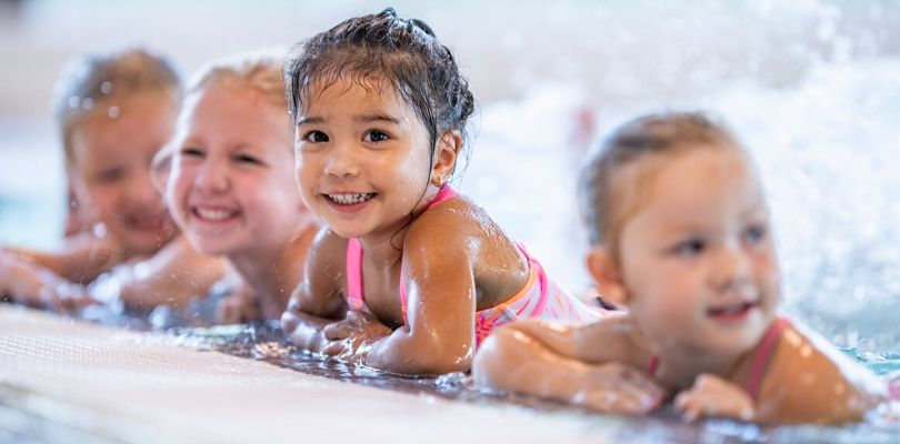 small children playing in the pool, an example of exercise for kids