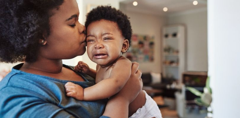 A mother soothing her crying baby.
