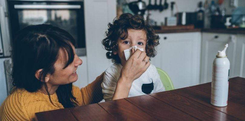 A mom blowing her sick son's nose.