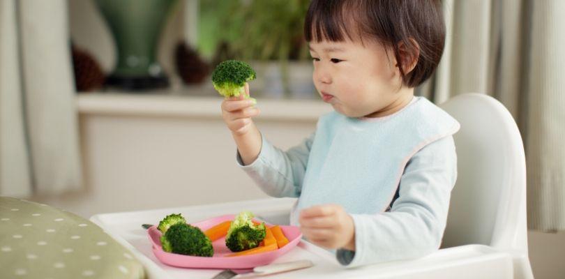 A toddler eating vegetables.