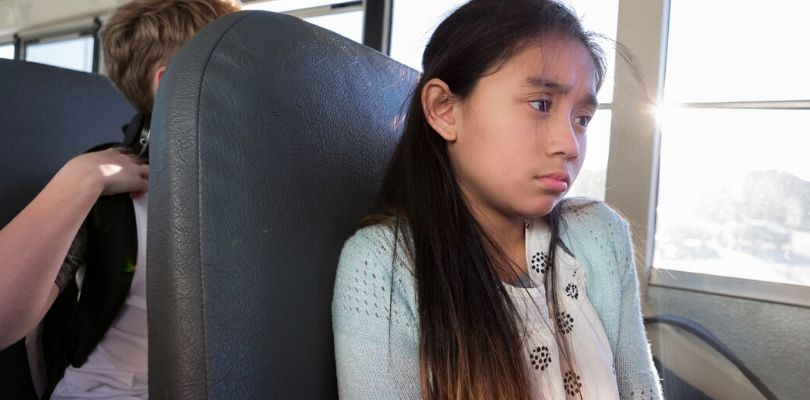 a child sitting on the bus, looking anxious and showing signs of anxiety