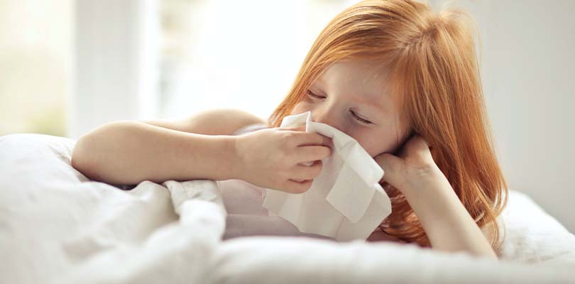 A child blowing her nose into a tissue.