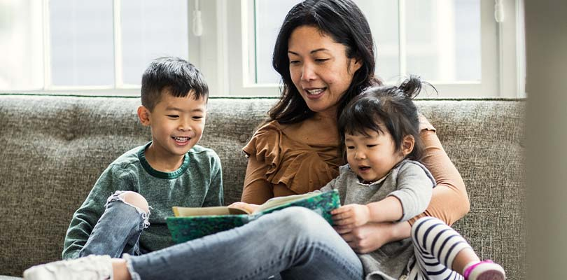 A family reading together on a couch.