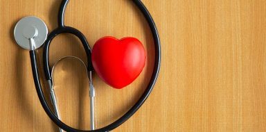 A foam red heart and a stethoscope against a wooden background.