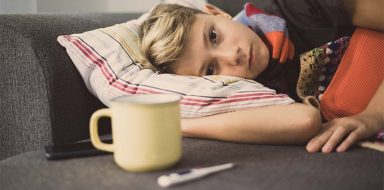 A boy laying on a couch sick.