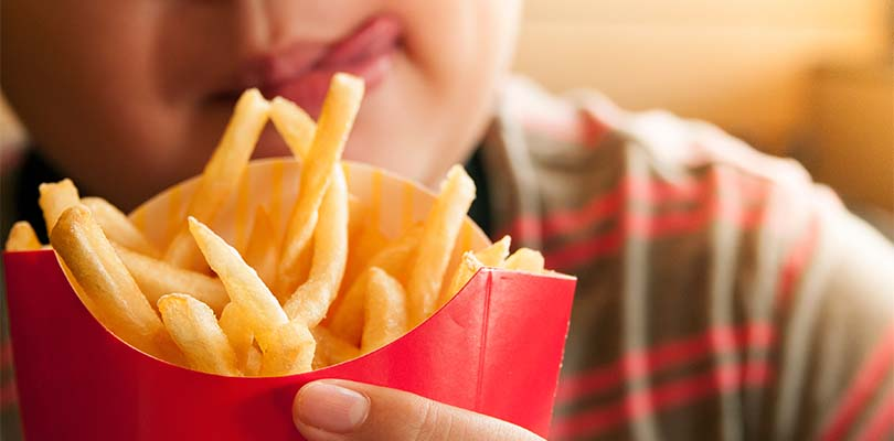 A child holding French fries.
