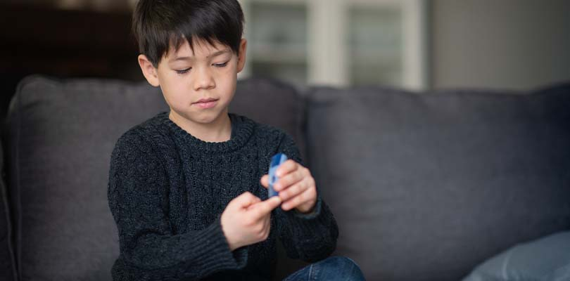 A child sitting on a couch checking their blood sugar levels.
