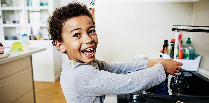A child washing their hands at a kitchen sink.