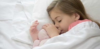 Achild sleeping in bed and sucking their thumb.