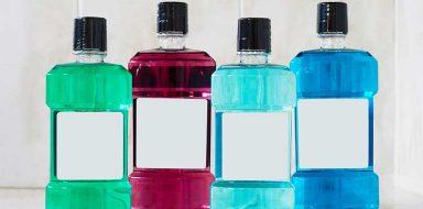 Green, pink, teal, and light blue bottles of mouthwash.