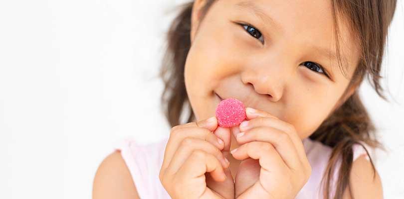 A child holding a pink, gummy multivitamin.