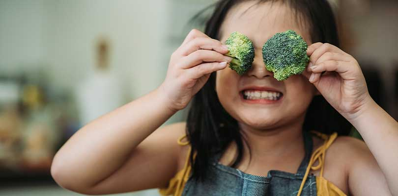 A little girl holding broccoli in front of her eyes.