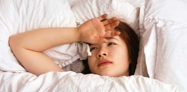 A teenage girl in bed with the back of her hand placed on top of her forehead.