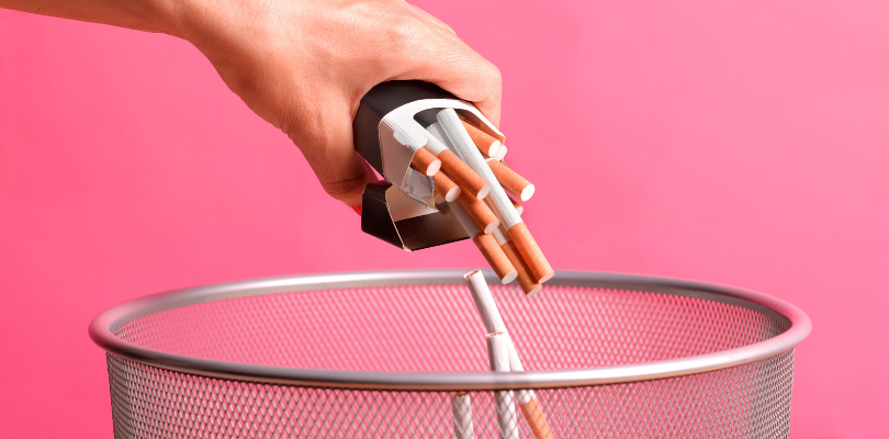 A person throwing a pack of cigarettes into a garbage can.
