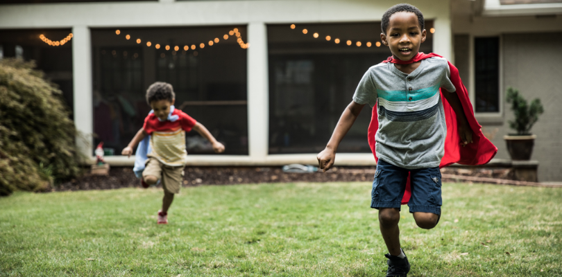 Two kids wearing capes running through a backyard.