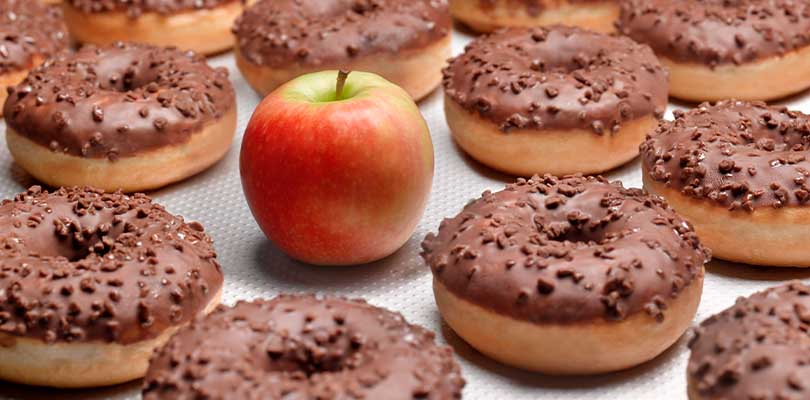 An apple surrounded by donuts.