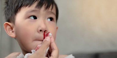 A mom wiping a child's nosebleed.